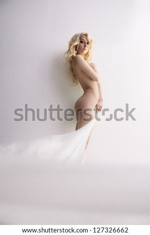 Sensual portrait of young attractive blond with transparent cloth over wall - stock photo