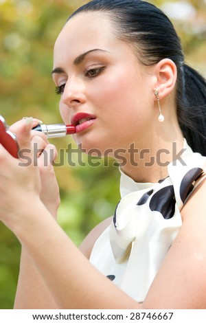 Sensual pretty woman applying cosmetics on her lips