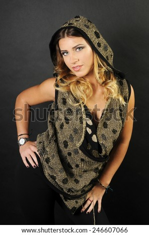 sensual provocative portrait of a beautiful smiling caucasian girl with long curly hair wearing Golden vest with black polka dots leaning forward with all her body with her hands on her hips - stock photo