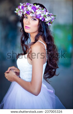 Sensual sexy beautiful curly girl in a white dress with a floral wreath on her head - stock photo