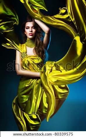 sensual sexy woman in green fabric on blue light - stock photo
