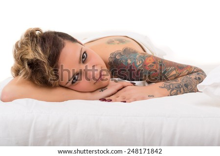 Sensual shot of a young tattooed woman in bed - stock photo
