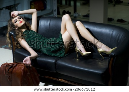 Sensual slender young blonde woman in green dress and gold shoes with brown bag lying on black leather sofa, horizontal picture - stock photo