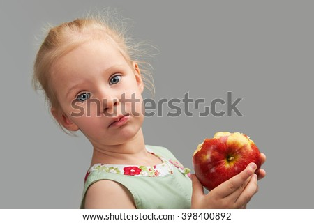 Sensual Studio Portrait of Blond young lady holding red apple at plain grey background