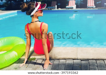 Sensual  tan slim woman in stylish red one-piece swimsuit  sitting on steps near pool  with  rubber ring, Outdoor fashion portrait of pretty lady enjoying  summertime  on her vacation. - stock photo