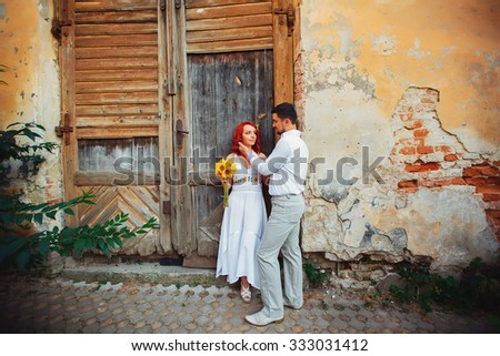 Sensual wedding Couple, groom and bride laughing near the brick wall, smiling and kissing