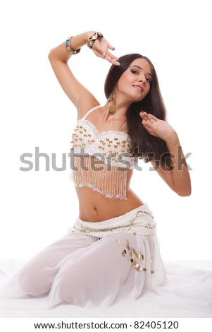 sensual woman belly dancer in white costume sitting on the floor isolated on white background - stock photo