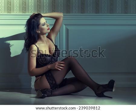 Sensual woman in underwear sit on floor at night, vintage style - stock photo
