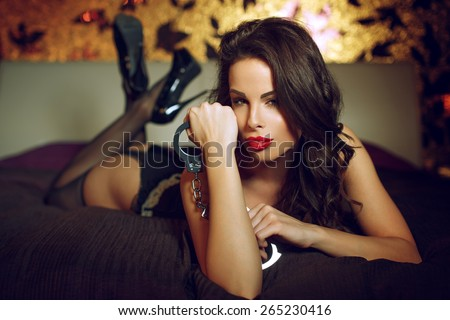 Sensual woman laying on bed with handcuffs, bdsm - stock photo