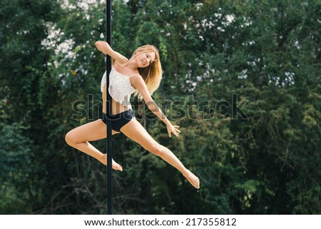 Sensual woman pole dancer performing outdoors in a park. - stock photo
