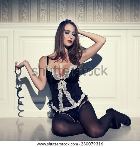 Sensual woman sit on floor and holding handcuffs, vintage style - stock photo