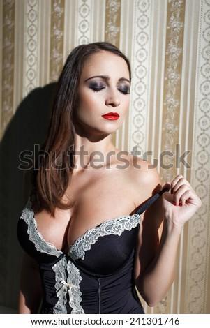Sensual woman take off corset at vintage wall, closed eyes, sensuality and desire - stock photo
