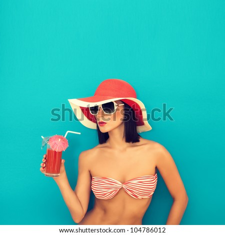 sensual woman with sunglasses drinking a cocktail - stock photo