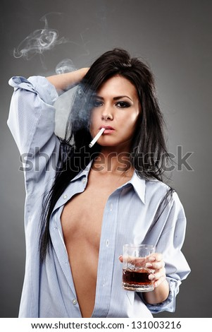 Sensual young woman in a man's shirt, smoking a cigarette and holding a glass of brandy, closeup pose on gray background, debauchery concept - stock photo