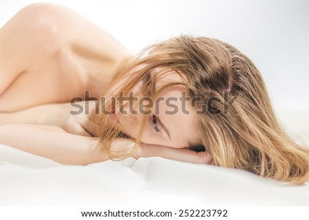 sensual young woman lying in bed  - stock photo