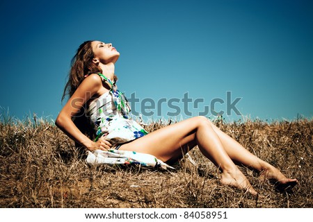 sensual young woman on summer field, blue sky in background, summer day - stock photo