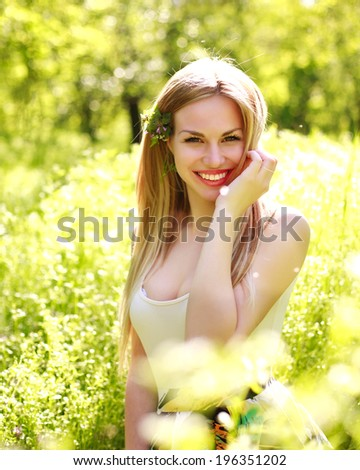 Sensual young woman, smiles sweetly in the flowered garden,  day dreaming  - stock photo