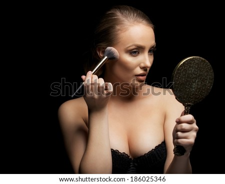 Sensual young woman wearing bra applying foundation on her face with a make up brush. Caucasian female fashion model holding mirror applying make up against black background. - stock photo