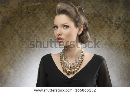 sensual young woman with brown creative hairdo posing in fashion shoot with black dress and bright big necklace   - stock photo