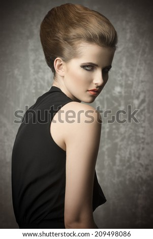 sensual young woman with charming eyes posing with stylish hair-style and make-up, wearing elegant black dress  - stock photo