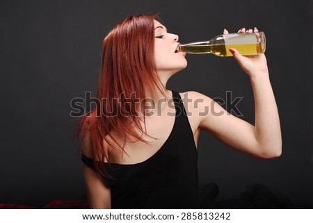 Sensual young woman with red hair and black shirt drinking a beer on black background - stock photo