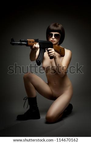 sensuality  beautiful sexy nude girl with submachine-gun, on dark background, glamour light - stock photo