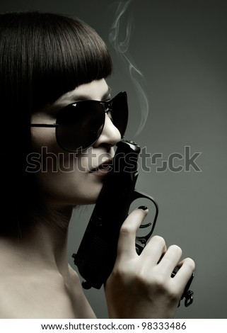 sensuality  beautifull  girl, close face , with pistol, on dark background, glamour light - stock photo