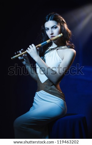 Sensuality beauty brunette plays a wooden flute