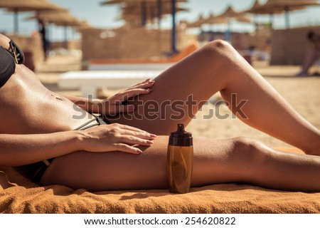Sensuous slim woman applying suntan lotion oil to her body at the beach - stock photo