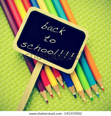 sentence back to school written in a blackboard label and some pencil crayons of different colors in a green background, with a retro effect - stock photo
