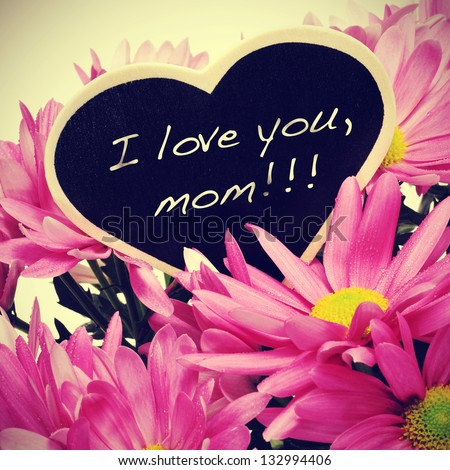 sentence I love you, mom written with chalk on a heart-shaped blackboard on a bouquet of pink chrysanthemums, with a retro effect - stock photo