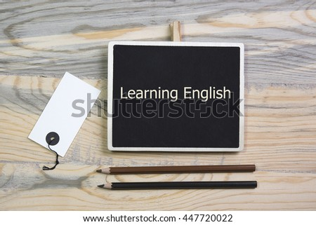 sentence Learning English written with chalk on a blackboard, on a table with pen.wooden desk - stock photo