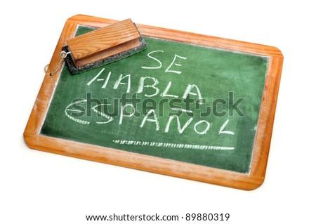 sentence Spanish is spoken written in spanish on a chalkboard - stock photo