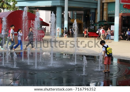 Sentosa, Singapore - July 19, 2017 : Kid taking a close look at fountain water at Sentosa island, Singapore