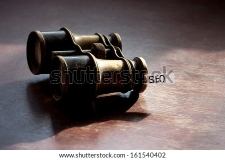 Seo concept with vintage binoculars. - stock photo
