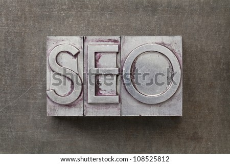 SEO (search engine optimization) acronym - text in vintage letterpress metal type against a grunge steel sheet - stock photo