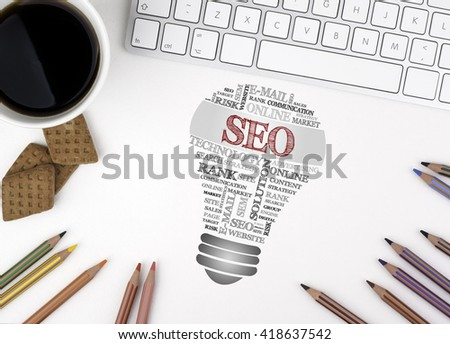 SEO (search engine optimization) bulb word cloud. White office desk - stock photo