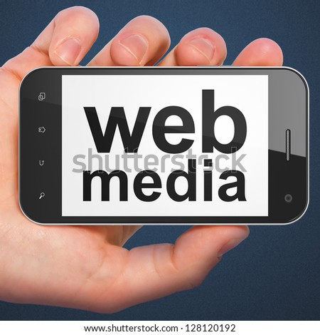 SEO web development concept: hand holding smartphone with word Web Media. Mobile smart phone in hand on Dark Blue background. - stock photo