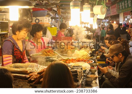 SEOUL, KOREA - OCTOBER 20, 2014 : Patrons enjoying street food lunch at Gwangjang Market, Seoul, Korea. - stock photo