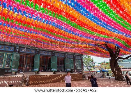 SEOUL, SOUTH KOREA - APRIL 19, 2016: People under paper lanterns at the Jogyesa Temple in Seoul, South Korea. Lanterns are set for the Lotus Lantern Festival, celebrating the Buddha's birthday.