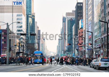 SEOUL, SOUTH KOREA - FEBRUARY 22: Pedestrians cross the street near Gangnam Station on February 22, 2014 in Seoul, South Korea. - stock photo