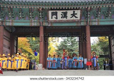 SEOUL, SOUTH KOREA - NOVEMBER 8, 2015: Armed guards in traditional costume guard the entry gate at Deoksugung Palace, a tourist landmark, in Seoul. November 8, 2015 Seoul, South Korea - stock photo