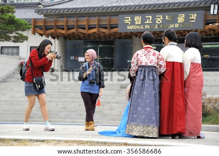 SEOUL, SOUTH KOREA-NOVEMBER 10: Girl taking pictures of friends in traditional costume. In front of the National Palace Museum of Korea. November 10, 2015 Seoul, South Korea