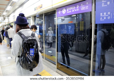 """SEOUL, SOUTH KOREA - NOVEMBER 11 : Girl walking in the Metropolitan Subway of Seoul with a backpack where a label is attached with text:""""Put it back, it's mine"""", November 11, 2015, Seoul, South Korea. - stock photo"""