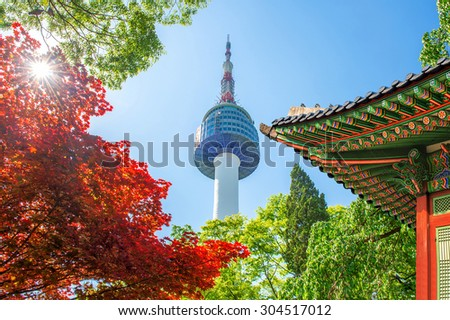Seoul Tower with gyeongbokgung roof and red autumn maple leaves at Namsan mountain in South Korea. - stock photo