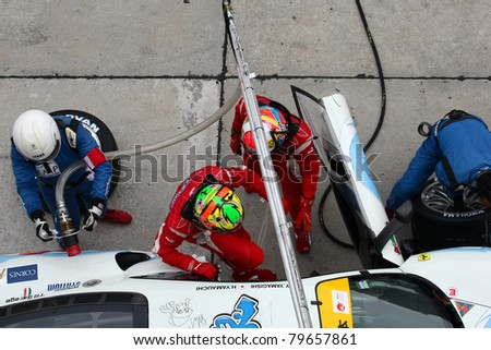 SEPANG - JUNE 19: LMP Motorsport team executes a drivers change during a pit-stop of the Japan SUPER GT Round 3 on June 19, 2011 in Sepang International Circuit, Malaysia. - stock photo
