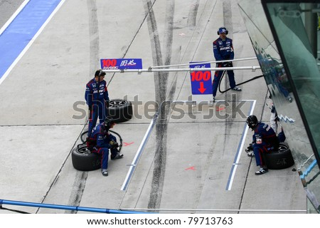 SEPANG - JUNE 19: Team Kunimitsu's pit-crew prepares for car to refuel, driver and tire change during the Japan SUPER GT Round 3 race on June 19, 2011 in Sepang International Circuit, Malaysia. - stock photo