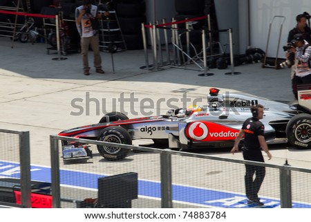 SEPANG, MALAYSIA - APRIL 8: British Lewis Hamilton of McLaren exists the pit garage for Friday practice at Petronas Formula 1 Grand Prix on April 8, 2011 in Sepang, Malaysia - stock photo