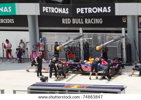 SEPANG, MALAYSIA - APRIL 8: German Sebastian Vettel of Red Bull Racing has a trial pitstop during Friday practice at Petronas Formula 1 Grand Prix on April 8, 2011 in Sepang, Malaysia - stock photo