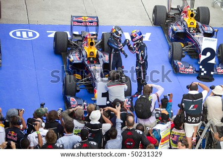 SEPANG, MALAYSIA - APRIL 4: German Sebastian Vettel of Team Red Bull congratulated by teammate Mark Webber after winning the race at the Petronas Formula 1 Grand Prix April 4, 2010 in Sepang, Malaysia - stock photo